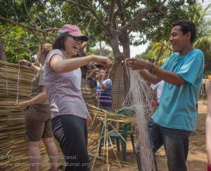 Juan showing a cultural tour participant how to make reed mats.